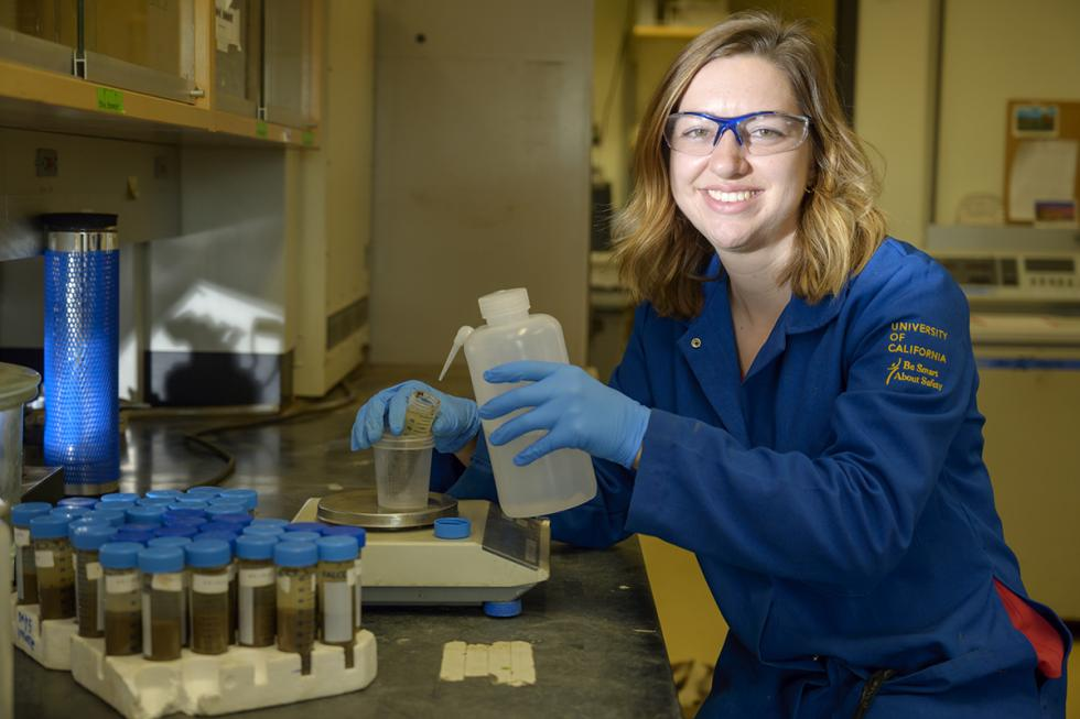 woman grad student in her lab and wearing blue lab coat