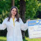 StarBio 2020 Big Bang! winner founders wearing lab coats, smiling while holding large award checks outdoors on grassy hills